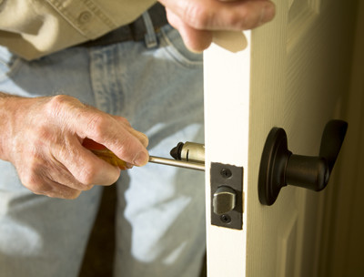 man unscrewing door knob